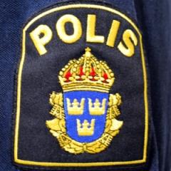 Polis, märke på uniform med text och symbol.